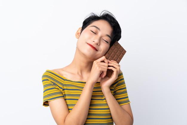 Jovem menina asiática tomando um comprimido de chocolate e feliz