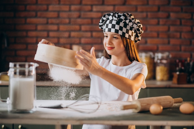 Jovem menina assando bolos na cozinha no café da manhã