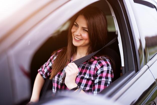 Jovem menina bonita alegre está afivelando-se em um assento de motorista de seu carro.