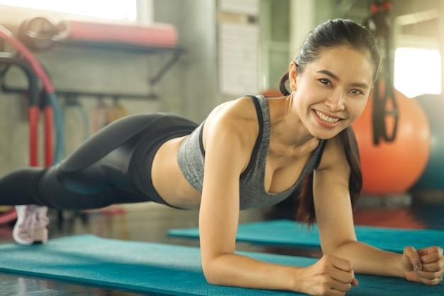 Jovem menina bonita asiática está fazendo uma prancha para treinamento de músculos abdominais