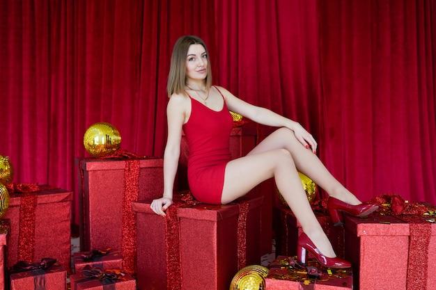 Jovem menina bonita bonita com caixas de presente vermelha. vogue moda estilo estúdio retrato de garota sexy vestido vermelho