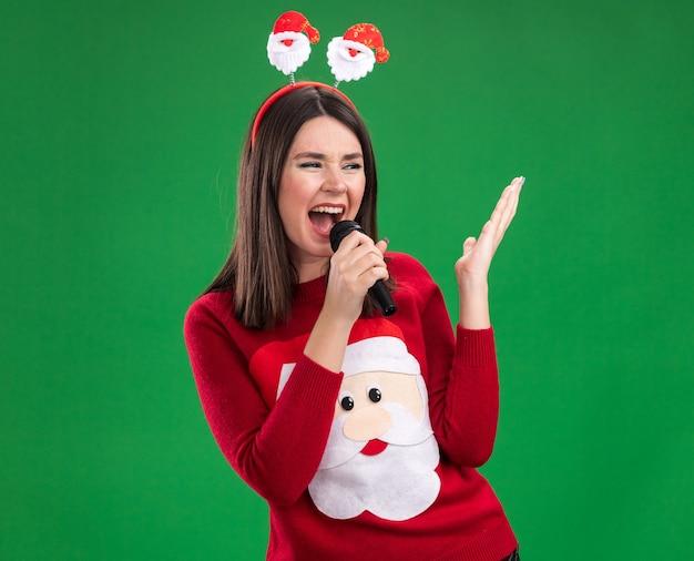 Jovem menina bonita caucasiana vestindo blusa de papai noel e bandana segurando o microfone, olhando para o lado, mantendo a mão no ar cantando isolada na parede verde com espaço de cópia