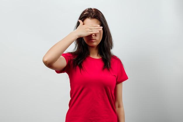 Jovem menina bonita cobre o rosto com as mãos
