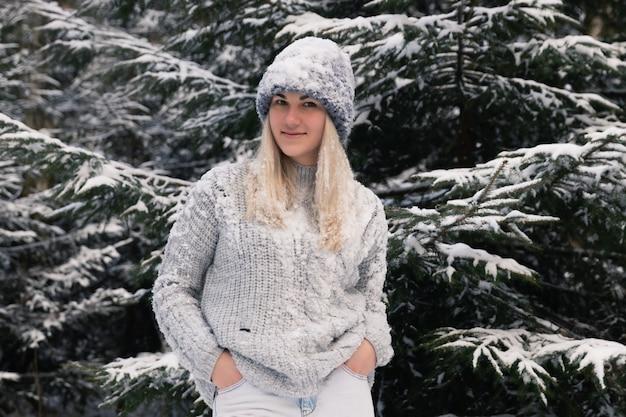 Jovem menina bonita com cabelo branco comprido joga bolas de neve. ela se diverte, joga neve e se alegra com a queda de neve. caminhada de inverno lá fora.
