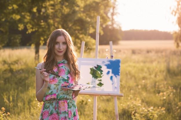 Jovem menina bonita com cabelo longo natural desenha uma imagem enquanto com um cavalete na natureza.