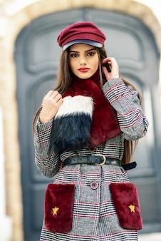 Jovem menina bonita com cabelo muito comprido, olhando para a câmera, vestindo casaco de inverno e boné ao ar livre.