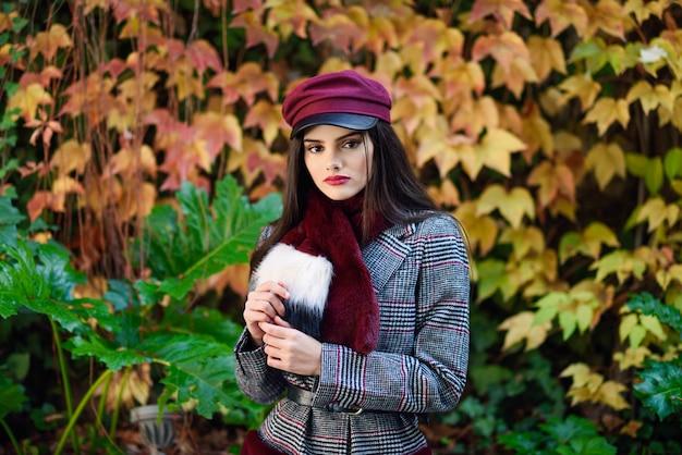 Jovem menina bonita com cabelo muito comprido, vestindo casaco de inverno e boné no fundo de folhas de outono