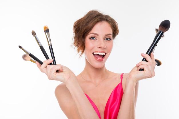 Jovem menina bonita com cabelos castanhos ondulados, pele limpa, dentes lisos, sorriso bonito, em jersey rosa, possui uma variedade de pincéis de maquiagem
