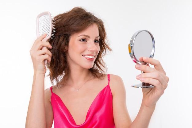 Jovem menina bonita com cabelos castanhos ondulados, pele limpa, dentes planos, sorriso lindo, em jersey rosa, com um cálculo e espelho calcula seu cabelo e sorrisos