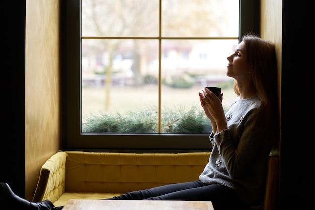 Jovem menina bonita com cabelos longos, bebendo café ou chá no café.