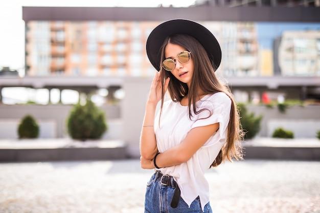 Jovem menina bonita com chapéu preto e óculos de sol ao ar livre na rua ensolarada