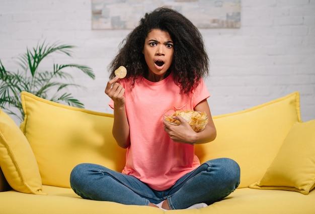 Jovem menina bonita comendo batatinhas, assistindo filme