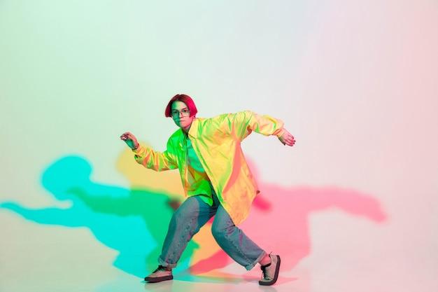 Jovem menina bonita dançando hip-hop, estilo de rua isolado no estúdio
