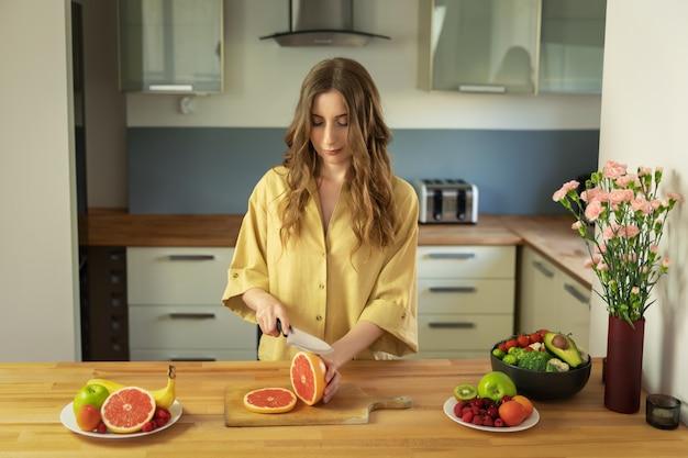 Jovem menina bonita é cortar uma toranja. uma mulher prepara uma salada de frutas deliciosa e saudável.