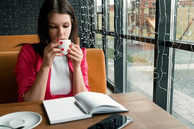 Jovem menina bonita, empresária bebendo chá ou café sentado no café