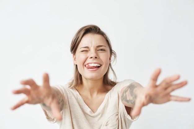 Jovem menina bonita engraçada piscando mostrando a língua esticando as mãos para a câmera.