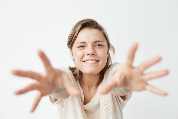 Jovem menina bonita engraçada sorrindo esticando as mãos para a câmera.