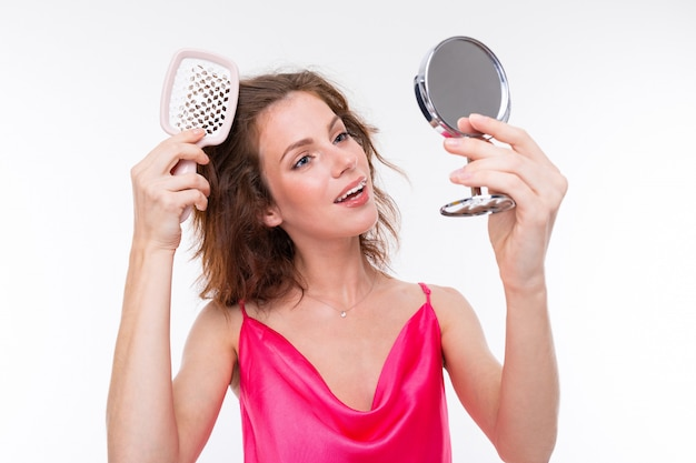 Jovem menina bonita escova o cabelo com pouco espelho isolado na parede branca