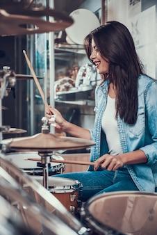 Jovem menina bonita está jogando no kit de bateria na loja de música