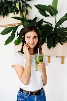 Jovem menina bonita falando do telefone móvel e bebendo batido em pé na mesa de um café