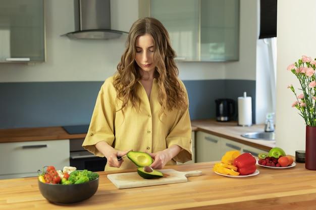 Jovem menina bonita fatias de abacate maduro. uma mulher prepara uma salada de legumes frescos e saudáveis.
