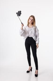 Jovem menina bonita fazendo auto-retrato com o smartphone anexado à vara de selfie