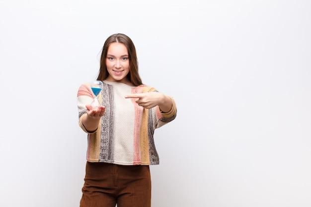 Jovem menina bonita loira segurando um relógio de areia temporizador