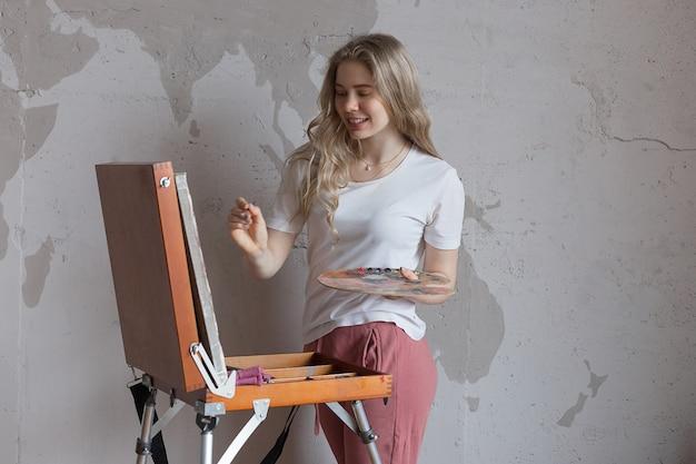 Jovem menina bonita loira sorridente com pincel e paleta em pé perto de imagem de desenho de cavalete