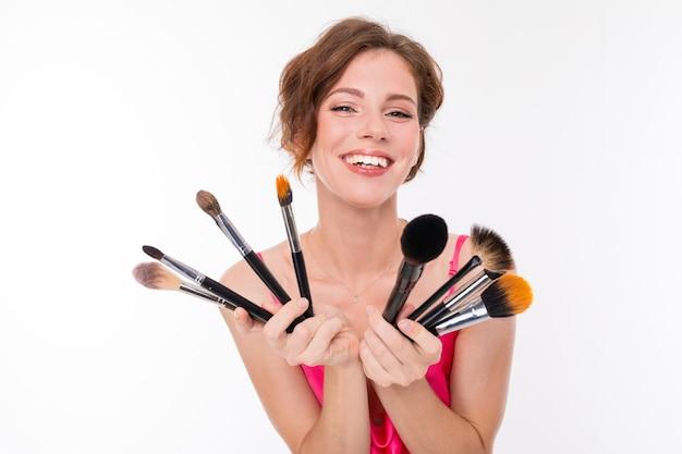 Jovem menina bonita mostra seus pincéis de maquiagem e sorriso isolado na parede branca