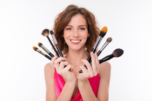 Jovem menina bonita mostra seus pincéis de maquiagem isolados na parede branca