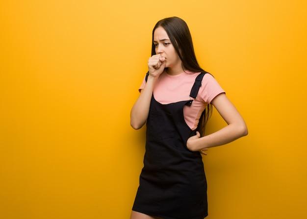Jovem menina bonita natural tossindo, doente devido a um vírus ou infecção