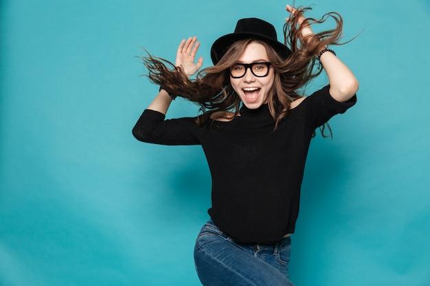 Jovem menina bonita no chapéu dançando e fazendo gestos de mão