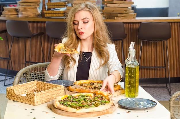 Jovem menina bonita olhando para um pedaço de pizza sem apetite