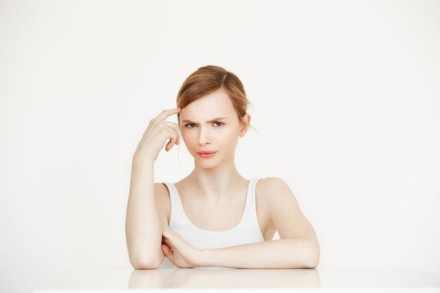 Jovem menina bonita pensando sentado à mesa. tratamento facial.