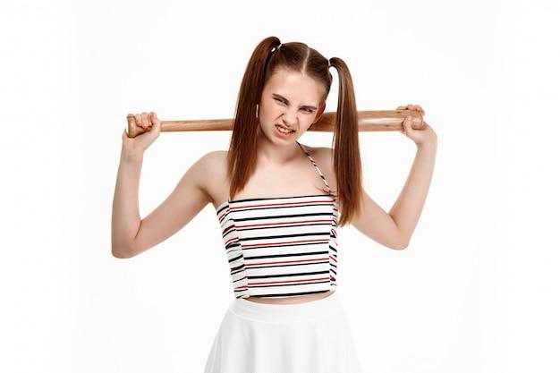 Jovem menina bonita posando com bastão, isolado na parede branca