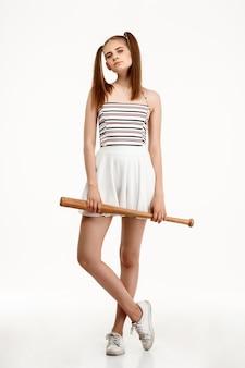 Jovem menina bonita posando com bastão sobre parede branca