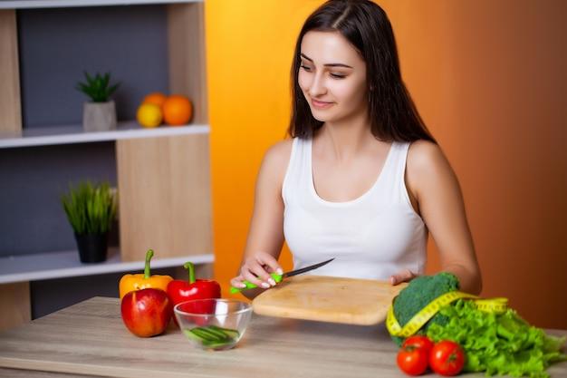 Jovem menina bonita prepara uma salada de dieta útil