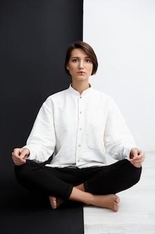 Jovem menina bonita sentada no chão sobre parede preto e branco