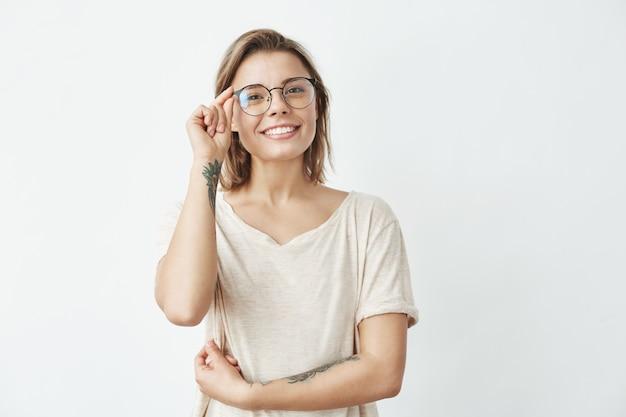 Jovem menina bonita sorrindo corrigindo óculos.