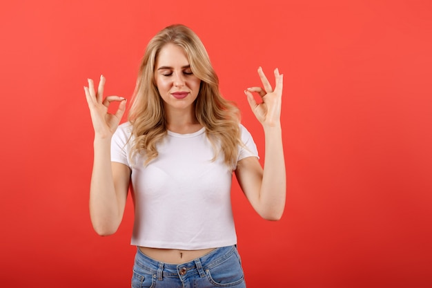 Jovem menina bonita vestindo camiseta casual em cima de fundo vermelho relaxar e sorrir