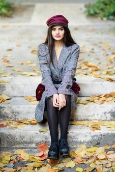 Jovem menina bonita vestindo casaco de inverno e boné sentado nos degraus cheios de folhas de outono