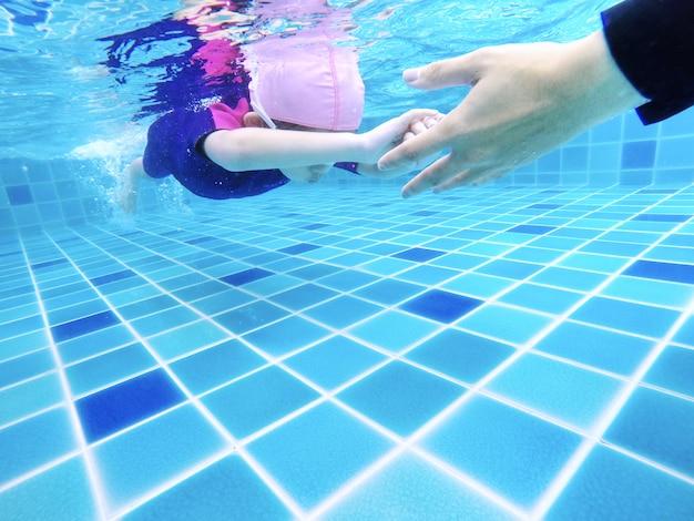 Jovem menina bonitinha debaixo d'água está nadando na piscina com seu professor de natação