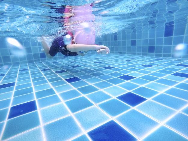 Jovem menina bonitinha debaixo d'água está nadando na piscina.