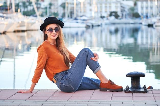 Jovem menina elegante em um porto marítimo