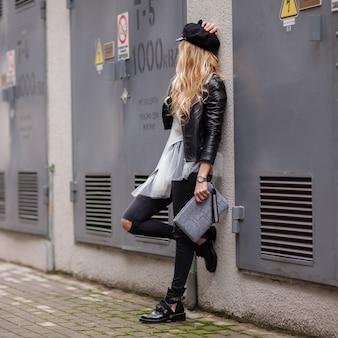 Jovem menina elegante em uma jaqueta de couro preta com uma bolsa cinza nas mãos dela parece longe