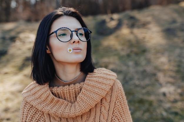 Jovem menina elegante na parede da floresta detém pequena margarida na mão e nos lábios. dia de sol e unidade com a natureza no ar fresco da floresta.