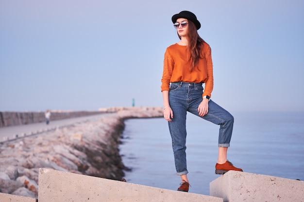 Jovem menina elegante posando em um porto marítimo