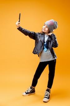 Jovem menina elegante tendo selfie