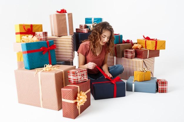 Jovem menina encaracolada bonita sentada no chão entre caixas de presente, abrindo um deles isolado