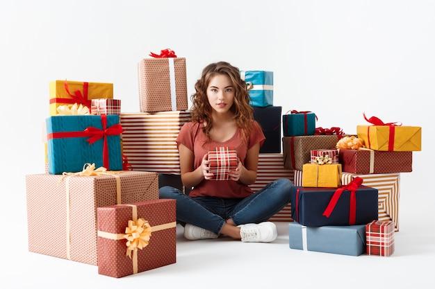 Jovem menina encaracolada bonita sentada no chão entre caixas de presente isoladas